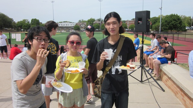 Three Chinese students enjoy their hamburgers at the BBQ